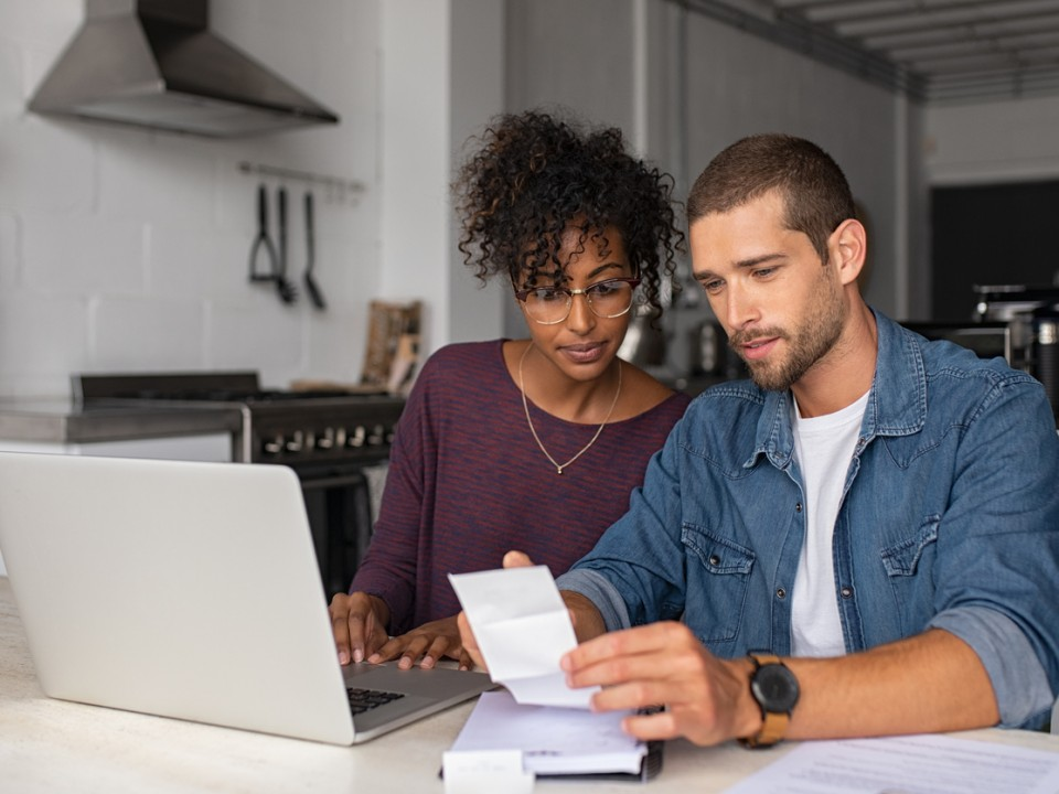 Couple looking at paperwork and laptop