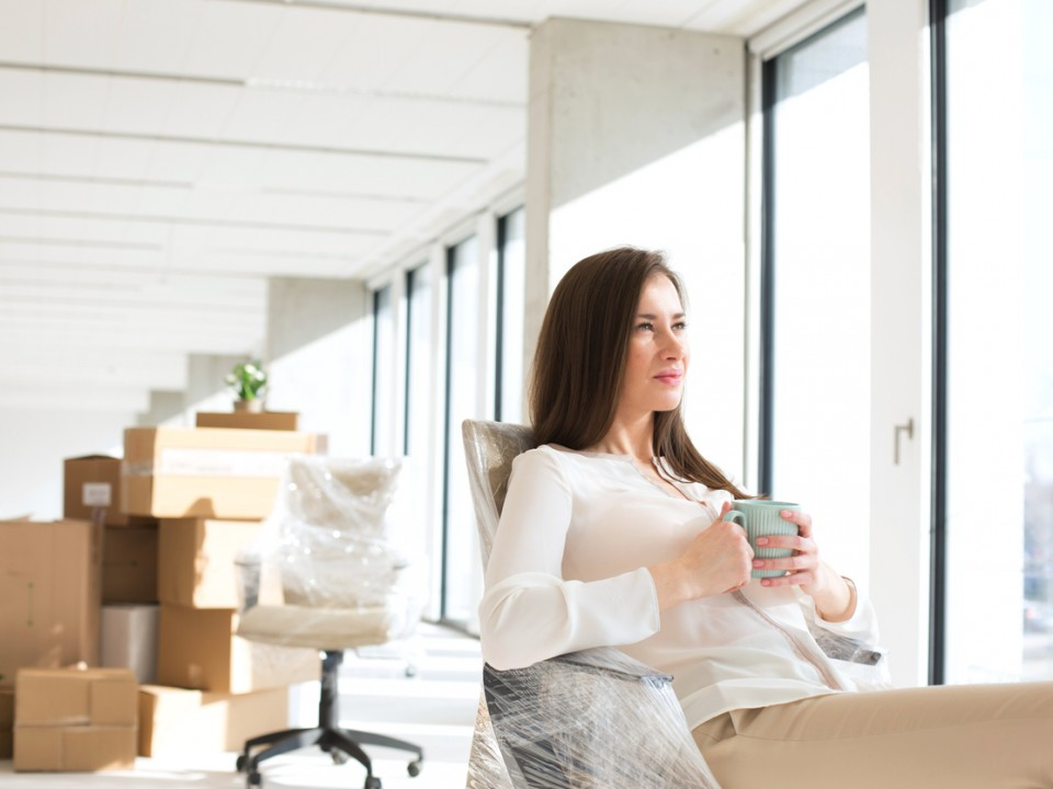 Young businesswoman having coffee in new office
