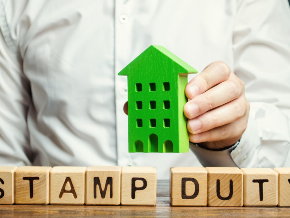 Businessman and wooden blocks with the word Stamp duty and house